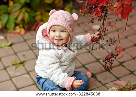 Very charming beautiful little girl with big brown eyes sits and smiles on the background of red leaves of grapes in autumn - stock photo
