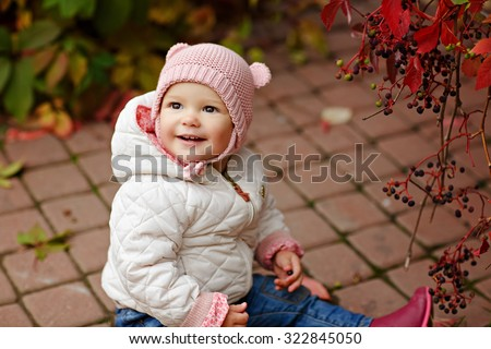 Very charming beautiful little girl with big brown eyes sitting, looking up and smiling on the background of red leaves of grapes in autumn