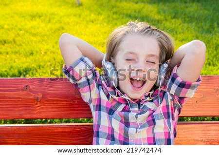 Very cheerful and funny little girl listening to music with headphones while sitting on a bench in the park. - stock photo