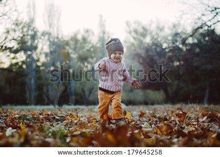 Very cheerful child having fun while tossing up leaves - stock photo