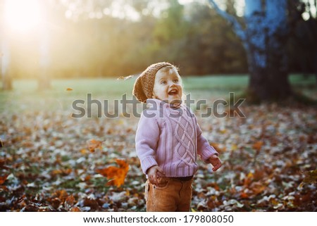 Very cheerful child having fun while tossing up yellow leaves