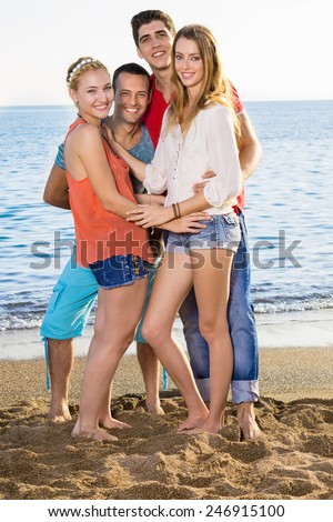 Very Close Happy Young Friends Standing on the Sand at the Beach on a Tropical Climate. - stock photo