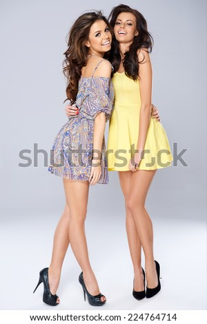 Very Close Pretty Smiling Ladies in Sexy Dress  Captured in Studio on Gray Background. - stock photo