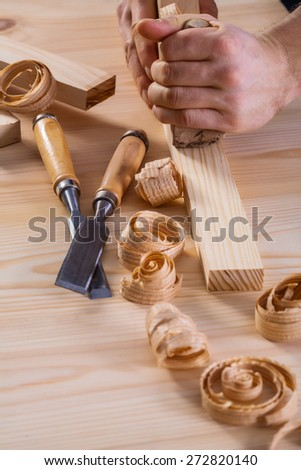 very close up view on hands of carpenter with woodworkers plane and chisels shavigs  - stock photo