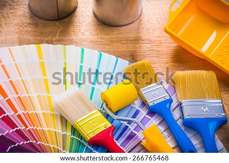 very close up view paint brushes roller tray on wooden board  - stock photo