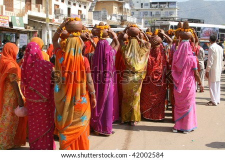 Very colorful ladies with pots on their heads - stock photo