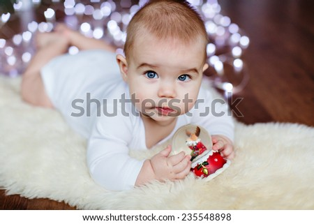 Very cute baby lying on the floor on the background of Christmas lights and holding a Christmas ball - stock photo