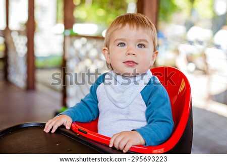 Very cute beautiful baby boy sitting in the highchair black