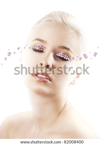 very cute blond young woman with hair style with some shining gem stone on her eyes as a creative make up
