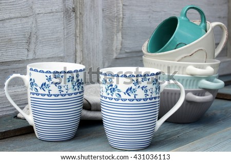 Very cute, home composition with kitchen ware on old wooden table. White, blue and grey color. Rustic lifestyle