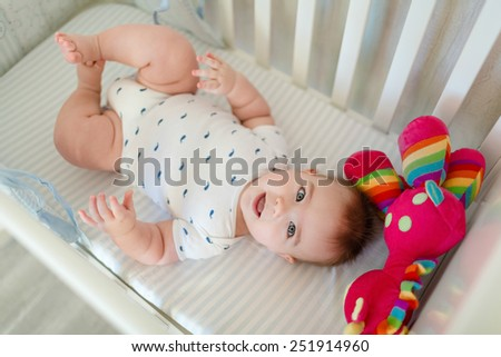 Very cute little baby boy lying on the bed at the back in the crib next to a bright toy - stock photo