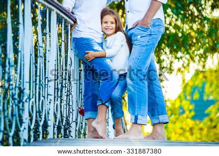 very cute little blonde girl holding the foot mom and dad. hug. - stock photo