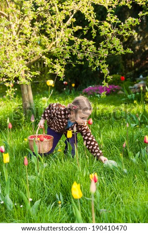 Very cute little girl collecting easter eggs in a flowering garden