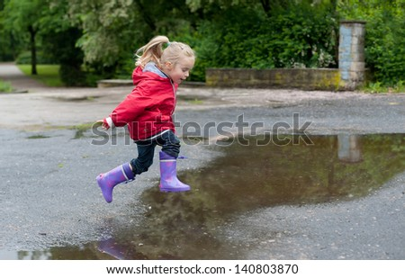 Very cute little girl in red Jacket, blue jeans and rubber boots is jumping over a puddle on a rainy day - stock photo