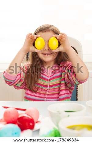 very cute little girl making colorful eggs for easter - stock photo