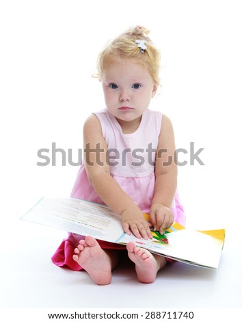 Very cute little girl reading a book sitting on the floor-Isolated on white background - stock photo
