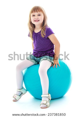 Very cute little girl sitting on a big ball sports. Happy childhood, fashion, autumnal mood concept. Isolated on white background - stock photo
