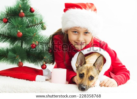 very cute little girl with a dog dressed in Christmas costumes - stock photo