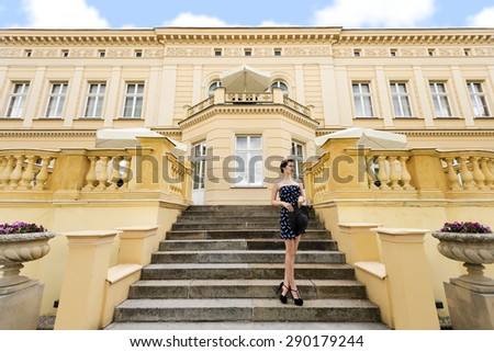 very cute princess in elegant blue dress with hat , standing on stairs of old bulding , outside and looking far away - stock photo