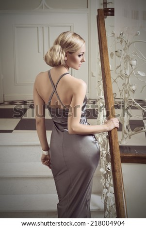 very cute woman , in evening dress going up stair in elegant indoor ambient, she has hair style . vintage color - stock photo