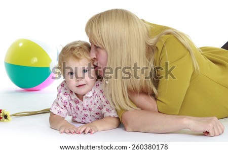 very delicate blonde mother kisses her little cute little daughter - isolated on white. - stock photo