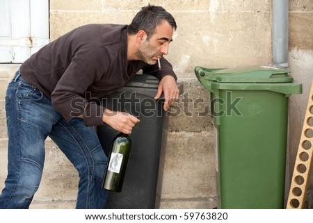 very drunk man smoking cigarette on trashcan