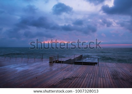 Very early morning at sea. a wooden desert pier and the dawn that is beginning to form. Black Sea.