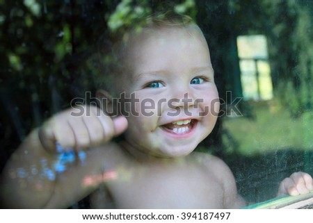 Very emotional little blue-eyed boy happily knocking on the window.