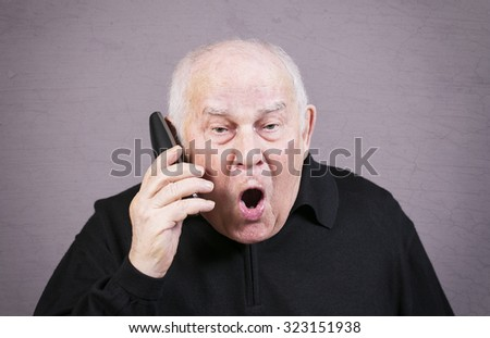 Very emotional old man gesticulates hands on a gray background