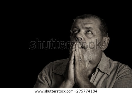 Very emotional sepia toned image of a praying senior man looking up