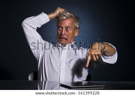 Very emotional upset frustrated senior business man pointing at his tablet computer lying on the desk while tearing at his hair with his hand - stock photo