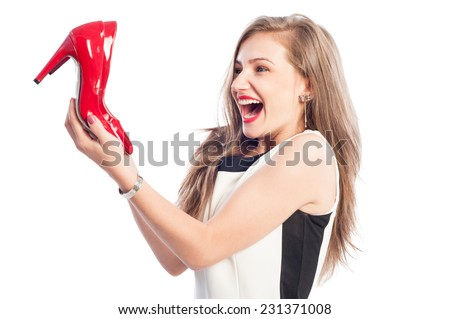 Very excited woman holding new high heel red shoes - stock photo