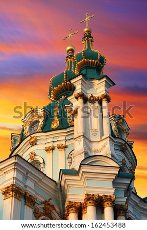 Very famous touristic place in Kiev - Church of St. Andrew over colorful sunset sky - stock photo