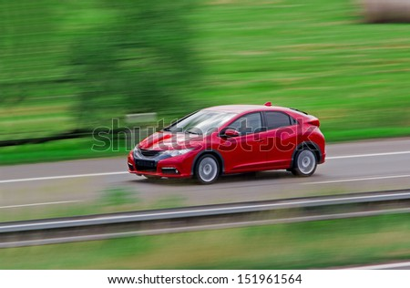 Very fast driving red Japanese modern hatchback - stock photo