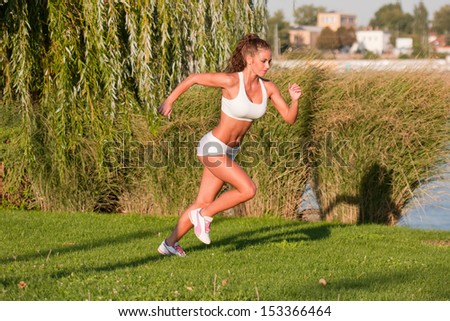 Very fit gorgeous young brunette woman exercising outdoors.