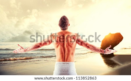 Very fit muscle man in tropical beach at sunset