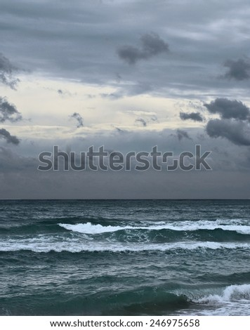 Very gloomy, overcast, cloudy sky over a dark stormy ocean.  While the waves are not huge, the presence of plenty of sea-form indicates the stormy conditions.  Vertical image of the Atlantic ocean. - stock photo