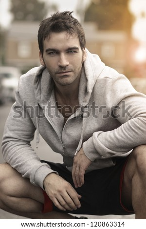 Very good looking man crouched down outdoors with nice relaxed expression - stock photo