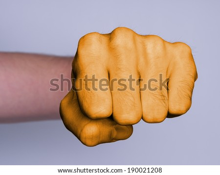 Very hairy knuckles from the fist of a man punching, orange skin - stock photo