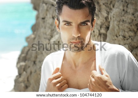 Very handsome young man pulling at white shirt outdoors in exotic beach setting