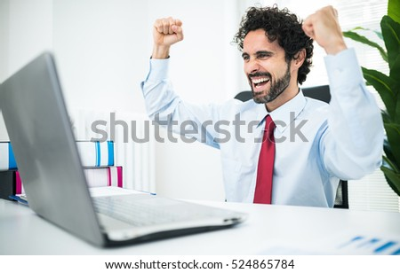 Very happy and excited businessman looking at his computer