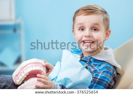 very happy boy after the doctor at the clinic, holding a dental  jaw in her hands and have a beautiful white smiles. Copy space - stock photo