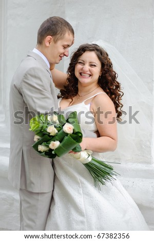 very happy bride  and groom standing arm in arm