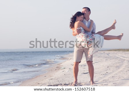 Very happy couple enjoy each other during sunset on the beach. Man holding woman on hands - stock photo