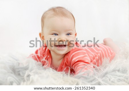 very happy cute little girl with wide smile on the white sofa - stock photo
