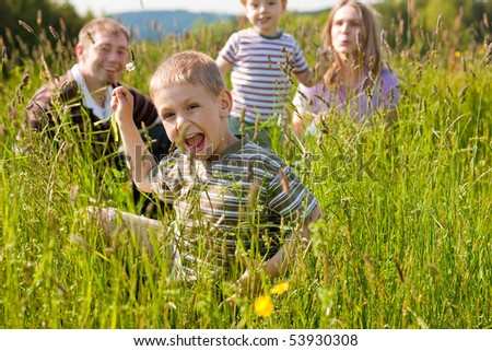 Very happy family with two kids sitting in a  meadow in the summer sun in front of a forest and hills, they are nearly hidden by the high grass, on boy is running towards the viewer