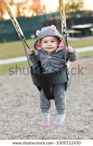 Very happy little girl on a swing in a mouse animal costume. Smiling one year old child.