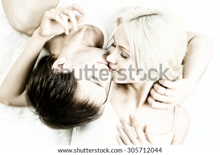 very happy  pretty couple, smile and kiss,  lie on white fur, close up - stock photo