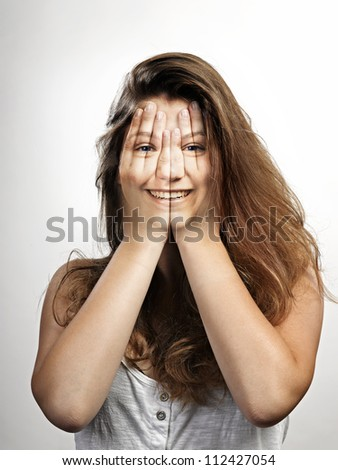 Very happy smiling or laughing (through hands) young beautiful woman - stock photo