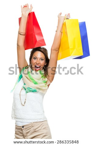 Very Happy Stylish Woman Raising Three Colored Shopping Paper Bag with Mouth Open and Looking at the Camera. Isolated on White Background.